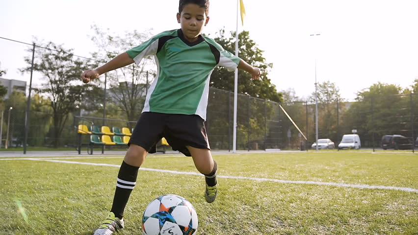 Young boy in the green uniform making exercise with soccer ball on the football field on the sunshine background. Dolly shot.