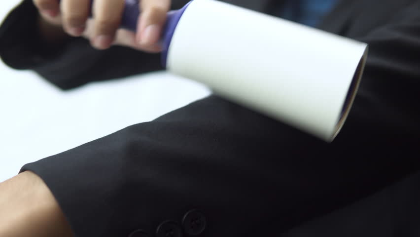 Woman using sticky lint roller cleaning sleeve of business suit jacket | Shutterstock HD Video #1020801895
