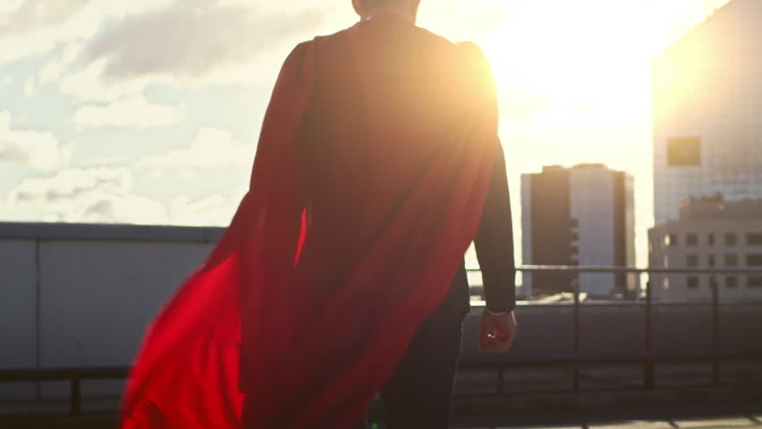 Superman WIth Red Cape Blowing in the Wind Walks on the Roof of a Skyscraper, Looking into the Sunset, Ready to Save the Day. Following Back View Slow Motion Shot. Royalty-Free Stock Footage #1020802285