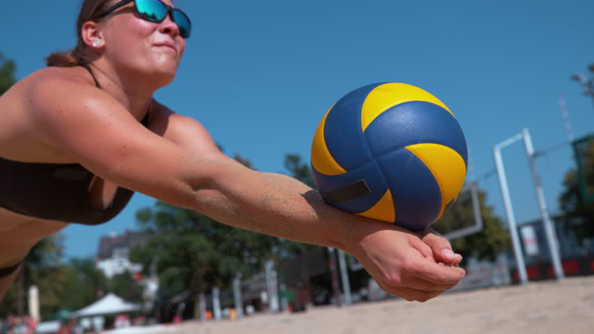 SLOW MOTION, CLOSE UP: Young woman falls into the sand while striking the ball with her hands. Athletic girl playing beach volleyball during her fun summer vacation. Female beach volleyball player.