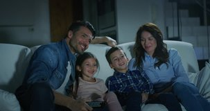 Portrait of happy family watching TV on sofa in the evening in living room in slow motion. Shot with RED camera in 8K. Concept of family entertainment, education, technology.