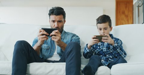 Portrait of happy father and son having fun using smart phone for playing game on sofa in living room in slow motion. Shot with RED camera in 8K.Concept of  family entertainment, education, technology