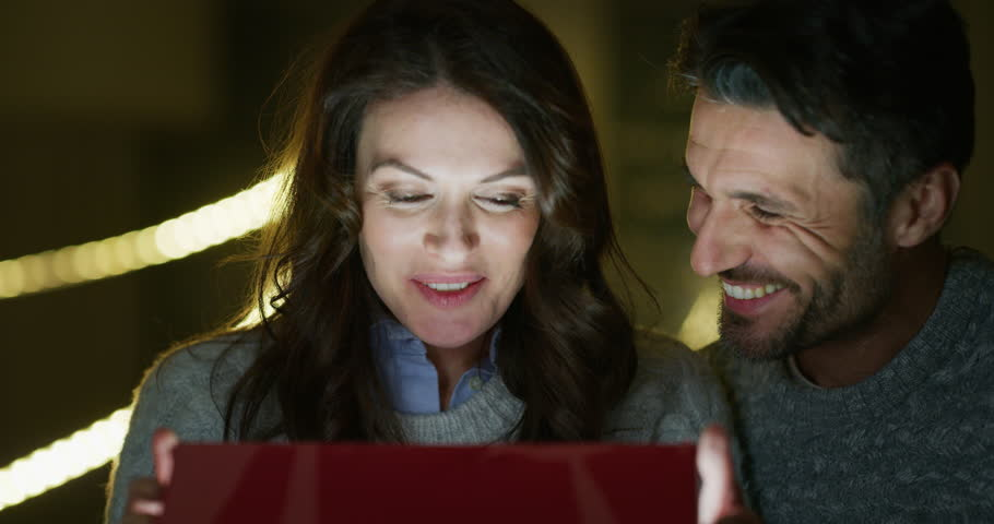 Portrait of a romantic couple opening a present gift box in the evening. Shot with RED camera in 8K. Concept of holidays, romance, surprise, e-commerce, online shopping.