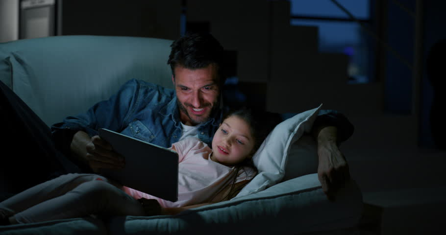 Portrait of happy father and daughter using a tablet on sofa in the evening in slow motion. Shot with RED camera in 8K. Concept of family entertainment, education, technology