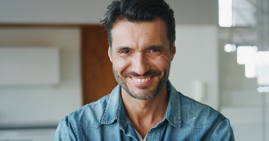 Portrait of a smiling handsome middle aged man in living room in slow motion. Shot with RED camera in 8K. Concept of lifestyle, achievement, father | Shutterstock HD Video #1020812488