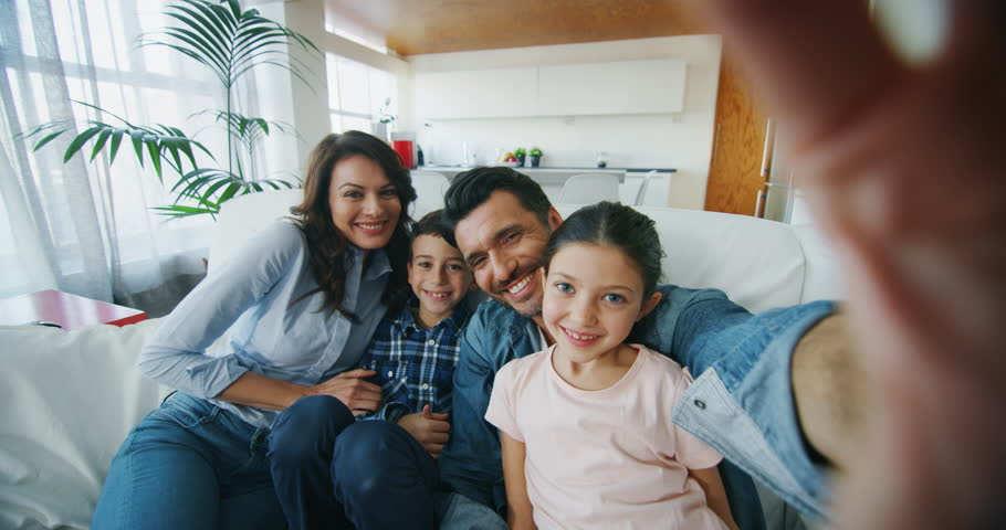 Portrait of happy family taking selfie in living room in slow motion. Shot with RED camera in 8K. Concept of communication, connection, technology, lifestyle, social, family.