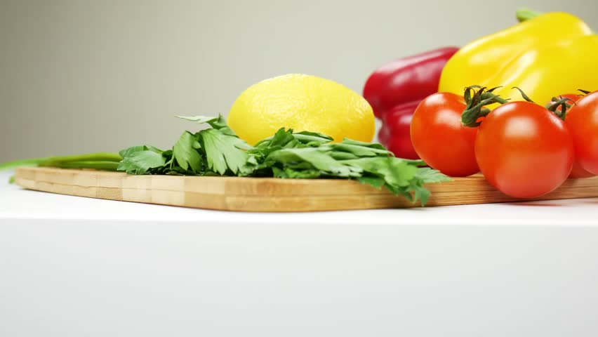 Healthy food. Vegetarian food. Ingredients for the salad on the table. Lettuce, cherry tomatoes, cucumber, red and yellow peppers, parsley. Glass bowl for salad. The camera moves from left to right | Shutterstock HD Video #1020821935