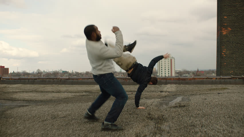 White man is knocked to the floor as he fights an African American man on a warehouse rooftop with skilled kicks and punches in overcast sunlight. Medium shot in 4K with an Alexa Mini camera