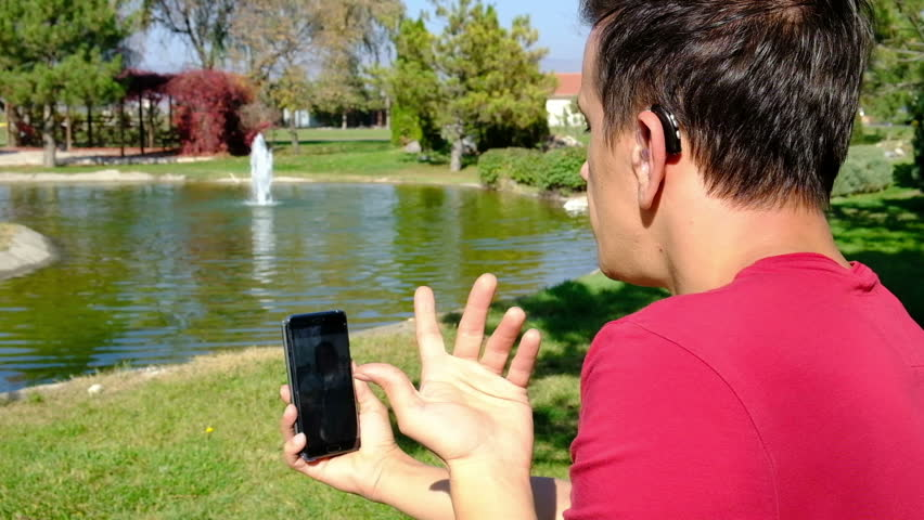 Young boy communicating with sign language  at smart phone