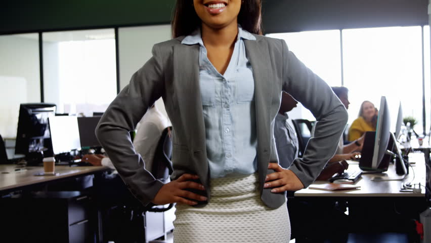 Portrait close up of a happy African-american businesswoman standing with hands on hip in office. The mixed race woman is smiling and laughing while looking at the camera. | Shutterstock HD Video #1020833353