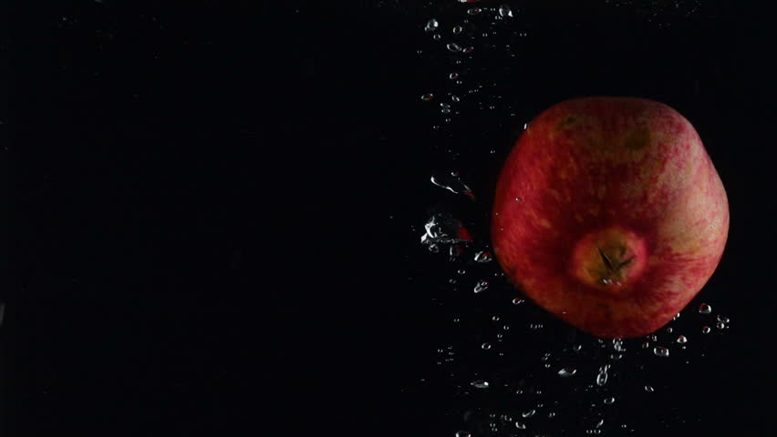 Pomegranate falls into the water on a black background | Shutterstock HD Video #1020834118
