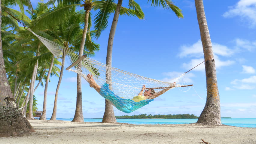 LOW ANGLE: Female traveler unwinds by the breathtaking ocean by taking an afternoon nap in a rope hammock. Relaxed woman enjoying her summer vacation on tropical island by swaying under the palm trees | Shutterstock HD Video #1020835420