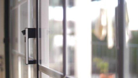 young man opening balcony sliding window door 4k