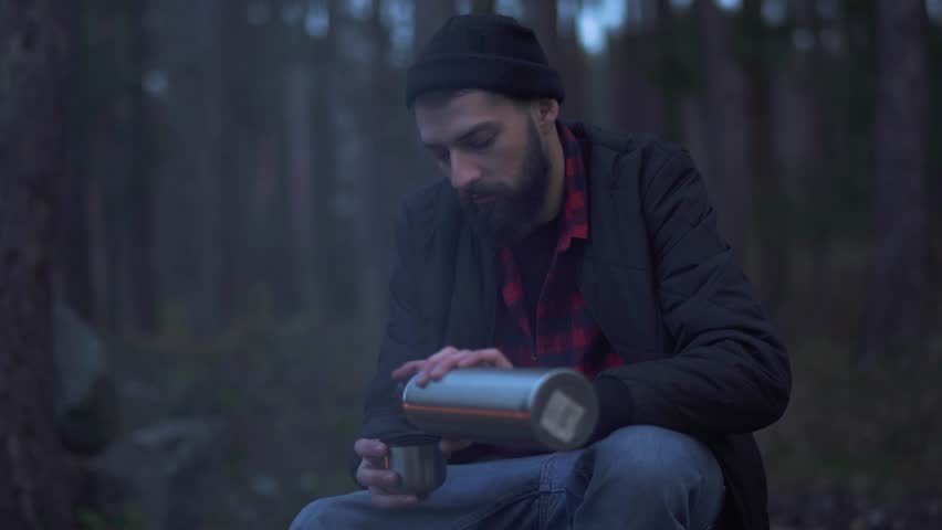 Young bearded man sit in the forest near bonfire and put beverage in a cup from thermos and drink. Brutal unshaven guy resting by the fire in the forest. | Shutterstock HD Video #1020843424