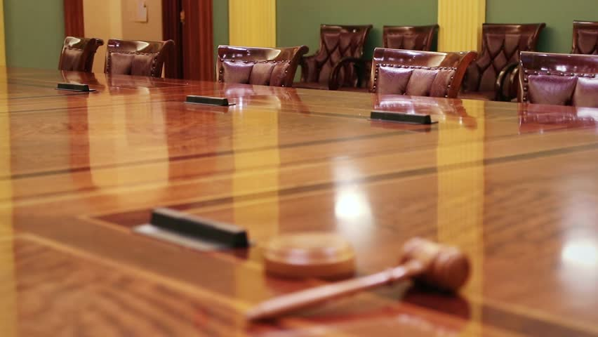 Wooden gavel resting on large table, with empty chairs in the distance. Royalty-Free Stock Footage #1020846337