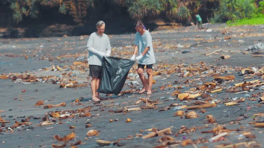 Group of volunteers cleaning up beach. The volunteer raises and throws a plastic trash into the bag. Environmental awareness and volunteering, recycling concept. Royalty-Free Stock Footage #1020850942