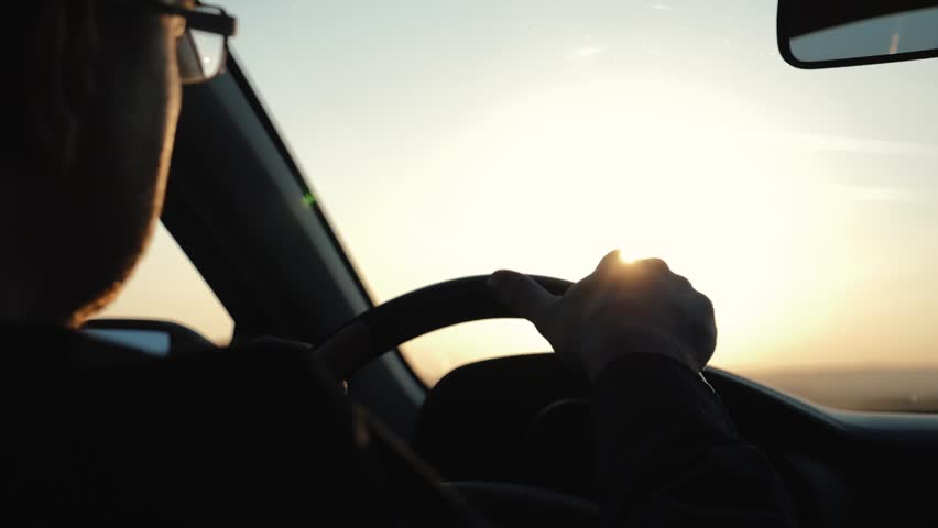 A man rides his car in the rays of sunset. Reflection in the rearview mirror | Shutterstock HD Video #1020854215