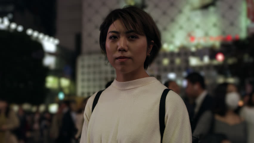 Portrait of a beautiful Japanese woman standing in the middle of a busy, crowded street in Shibuya with soft dark, natural lighting. Medium shot on 4k RED camera on gimbal.