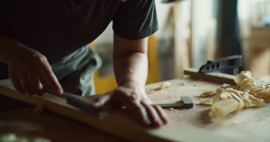 Female woodworker carves wood piece in well lit workshop during the day. Long to medium shot with soft lighting