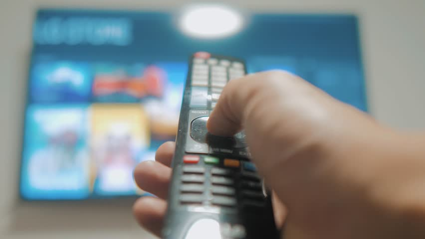 Smart tv with apps and hand. Male hand holding the remote control turn off smart tv . man hand controls TV holding remote. TV lifestyle concept internet online cinema | Shutterstock HD Video #1020911086