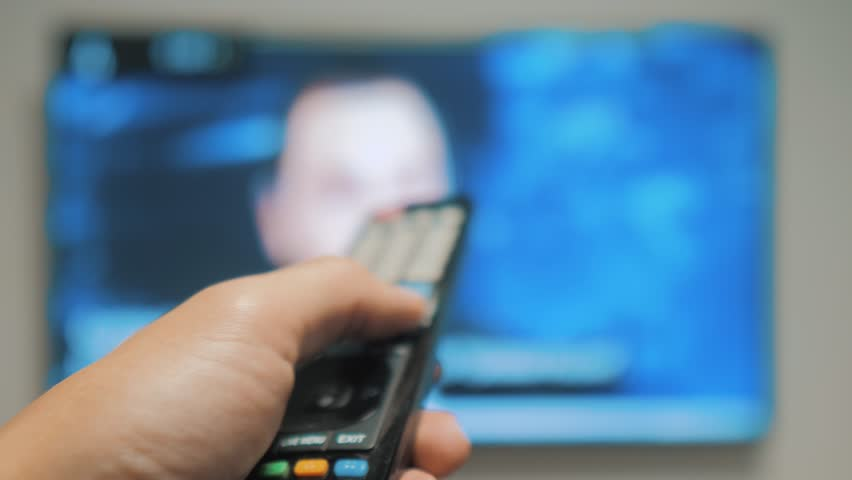 Man hand holding the TV remote control and turn off smart tv . Channel surfing . Close up mans hand holding TV remote control and changing. blurred background lifestyle TV channels | Shutterstock HD Video #1020911089