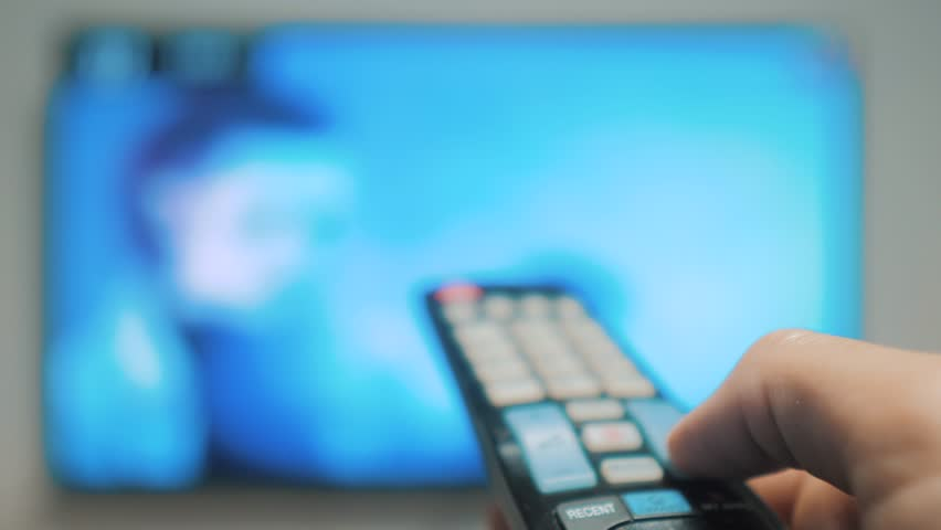 Man hand holding the TV remote control and turn off smart tv. Channel surfing lifestyle . Close up mans hand holding TV remote control and changing TV channels. blurred background | Shutterstock HD Video #1020911098
