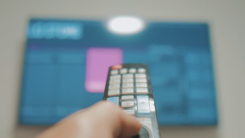 Smart tv with apps and hand. Male hand holding the remote control turn off smart tv. man hand controls TV holding remote. concept lifestyle internet online cinema | Shutterstock HD Video #1020911101
