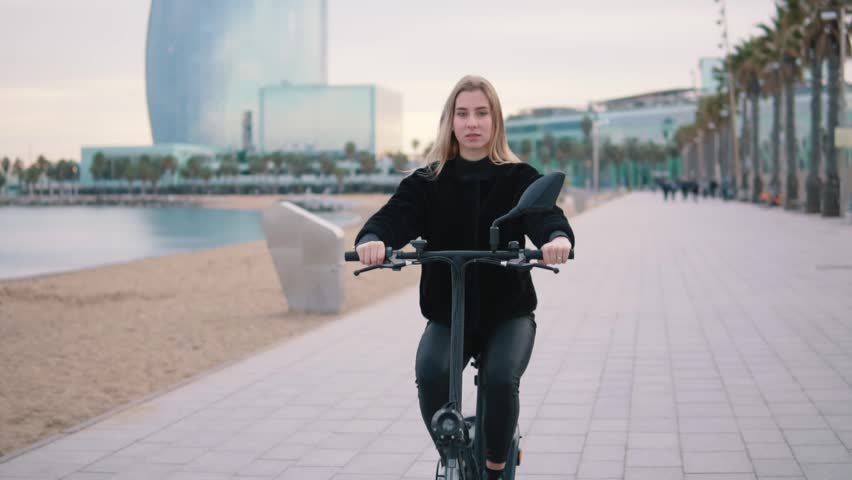 Pretty blonde woman driving electric bike near sea. Modern city transportation #1020925363