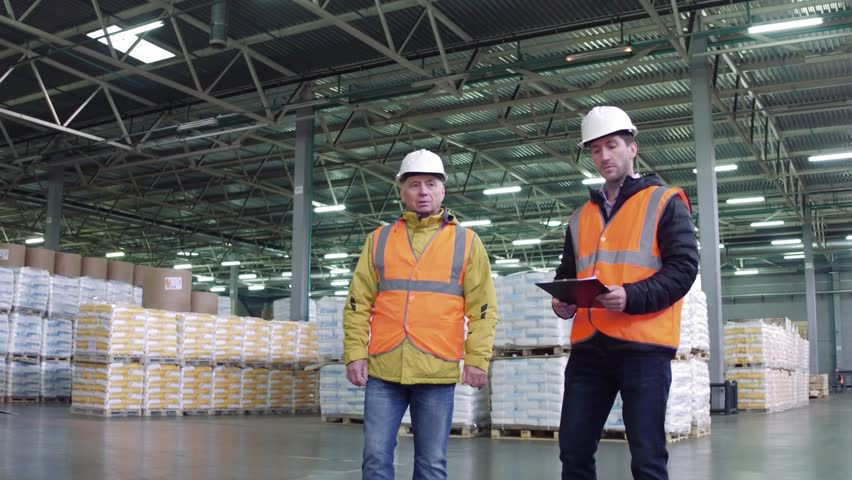 Workers walking and discussing stock inventory against tall shelves, in a warehouse with bright lamps. | Shutterstock HD Video #1020927820