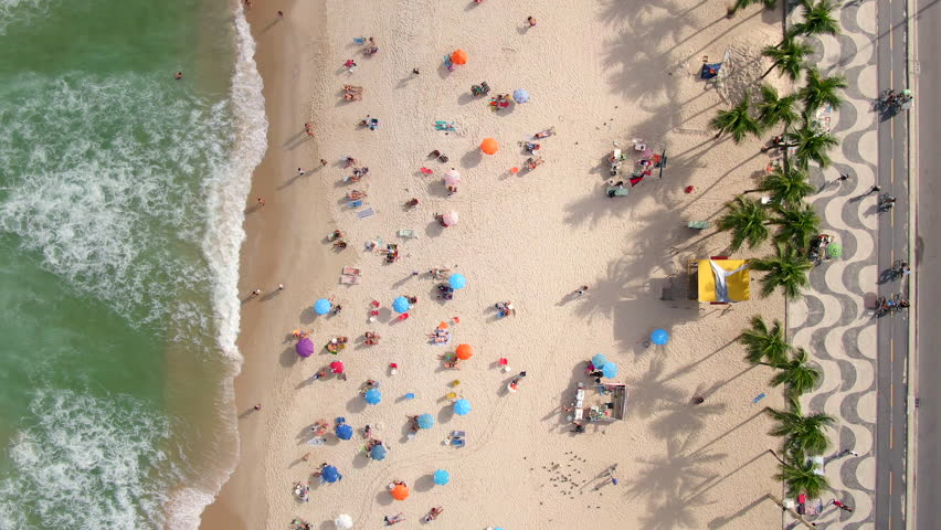 Copacabana beach in Rio de Janeiro, Brazil, top aerial view of waves crashing on the beach with people and umbrellas on the shore on a beautiful summer day.