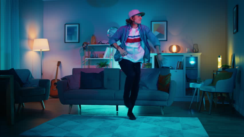 Handsome Excited Hip Young Man is Dancing in the Living Room while TV Plays in the Background. He is Energetically Moving while Screen Adds Reflections on Him. Cozy Room is Lit with Warm Neon Light.