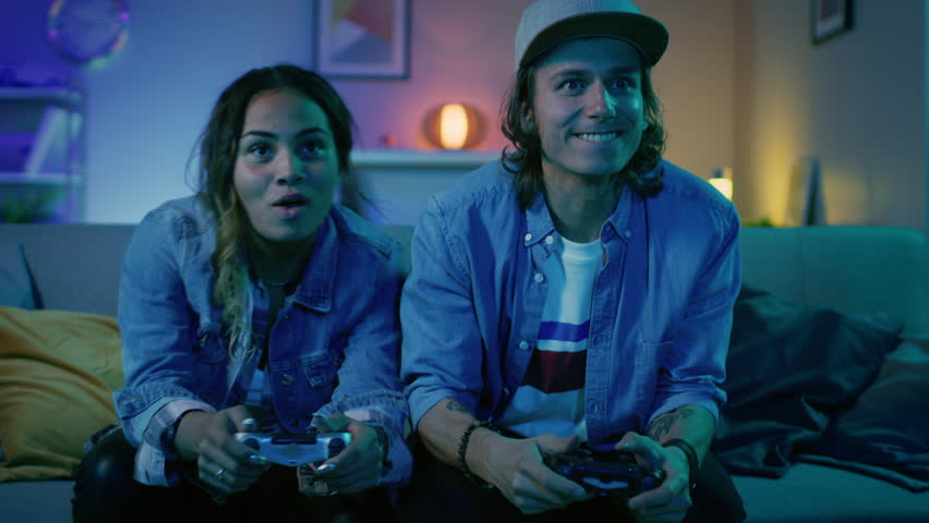 Excited Black Gamer Girl and Young Man Sitting on a Couch and Playing Video Games on Console. They Plays with Wireless Controllers. Cozy Room is Lit with Warm and Neon Light.