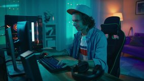 Excited Gamer Playing and Winning in Online Video Game on His Personal Computer. Room and PC have Colorful Warm Neon Led Lights. Young Man is Wearing a Cap. Cozy Evening at Home.