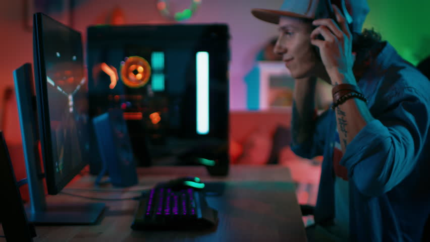 Gamer Puts His Headset with a Mic On and Starts Playing Shooter Online Video Game on His Personal Computer. Room and PC have Colorful Neon Led Lights. Young Man is Wearing a Cap. Cozy Evening at Home. Royalty-Free Stock Footage #1020931093