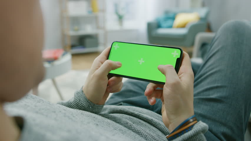 Man at Home Lying on a Couch using Smartphone, Holds it Horizontally in Landscape Mode. Pushing Buttons to Play Video Game. Screen Has Tracking Markers. Point of View Camera Shot.