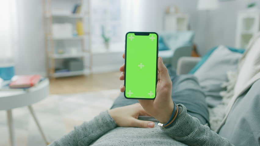 Man at Home Lying on a Couch using Smartphone with Green Mock-up Screen, Doing Swiping, Scrolling Gestures. Screen Has Tracking Markers. Point of View Camera Shot. | Shutterstock HD Video #1020934159