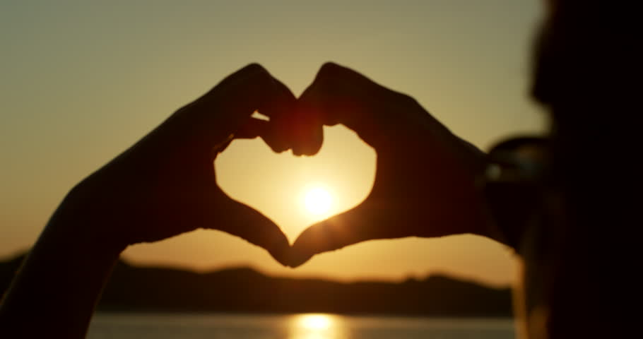Close up of young woman making heart shape with her hands against sky. Woman is catching the setting sun with her heart shaped fingers. Female is making symbol of love. Shot on RED Camera.