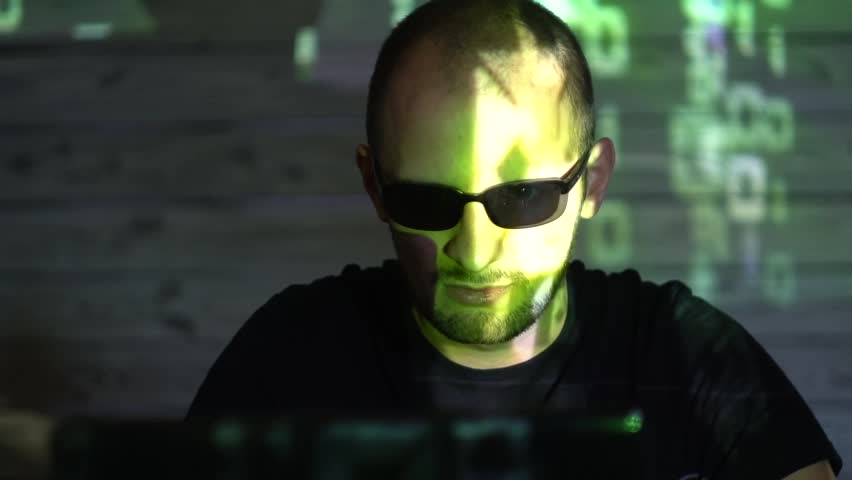 A man hacker man in sunglasses in a dark room works with the program code | Shutterstock HD Video #1020939235