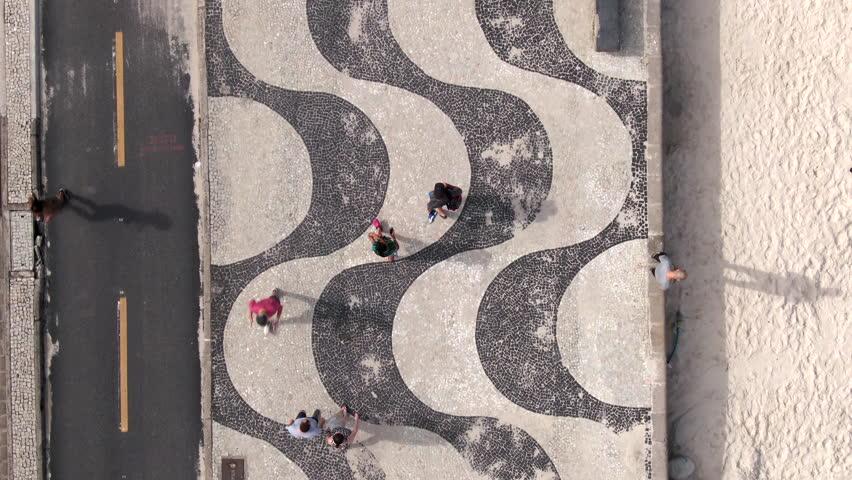 Rio de Janeiro, Brazil, flying directly above the iconic Copacabana Beach mosaic sidewalk. Royalty-Free Stock Footage #1020943855