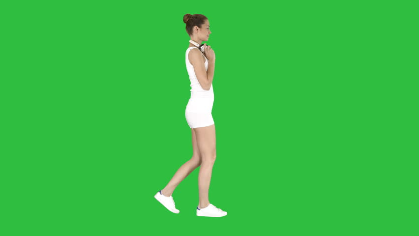 Woman in white shirt listening for the music using headphones and walking on a Green Screen, Chroma Key.   Shutterstock HD Video #1020957775