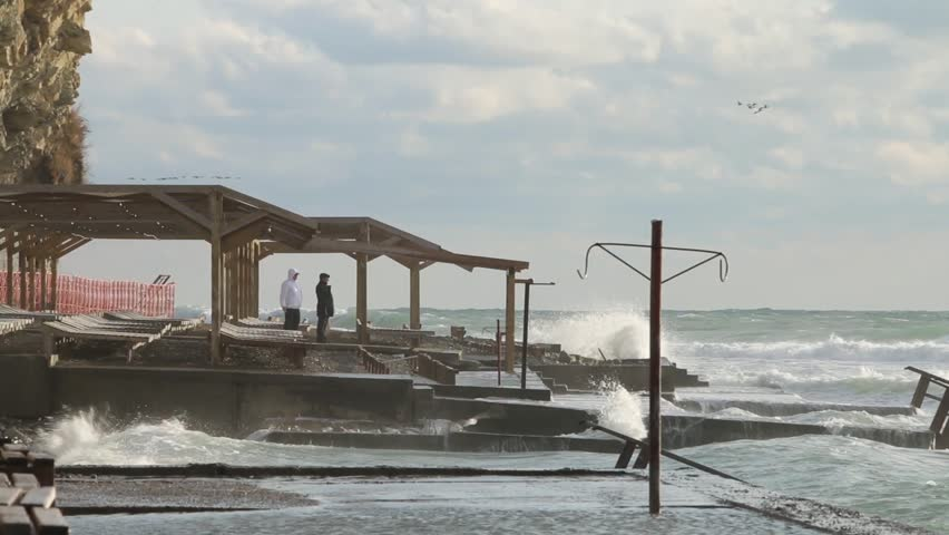People seeing at the sea storm. Huge powerful waves breaking at seawall in major severe storm. Russia, Anapa city