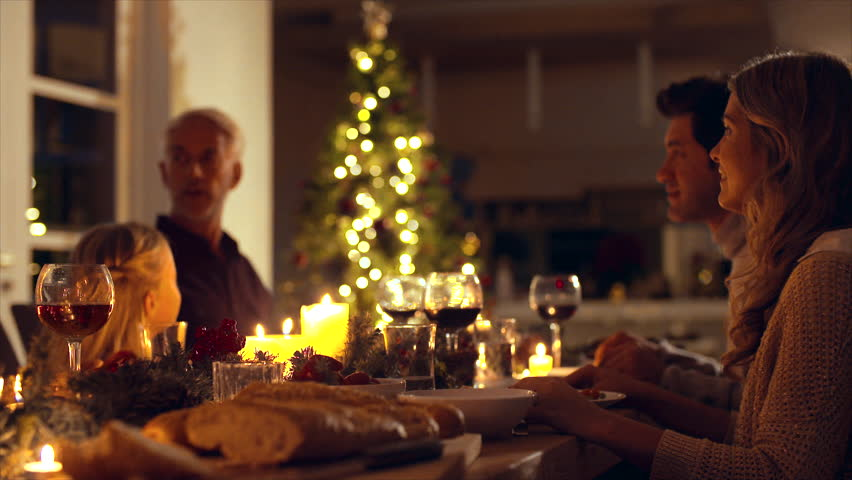 Happy family celebrating christmas together at home. Family sitting at dining table talking and having dinner together on Christmas eve.  | Shutterstock HD Video #1020996595