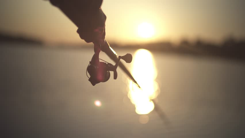 Male hand holds fishing rod on the background of the river during sunset close-up. Fisherman holds a fishing rod against the sunset. Sunlight through a fishing rod. River fishing.