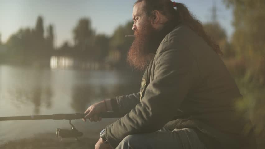 Bearded fisherman fishing on the lake. Fisher smokes sigarrette on fishing. | Shutterstock HD Video #1020996751