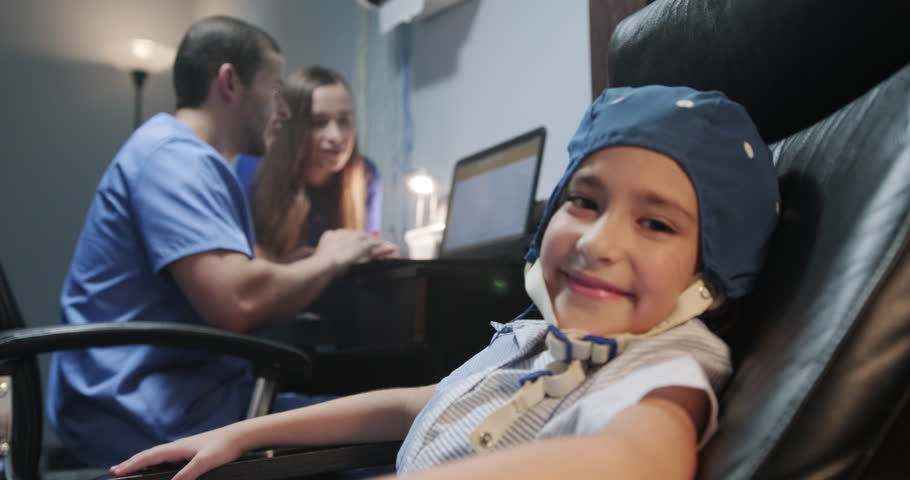 Portrait of young preteen autistic girl looking at camera in slow motion, while medical staff and mother reads EEG results on computer. The girl smiles while doing electroencephalogram Royalty-Free Stock Footage #1020997996