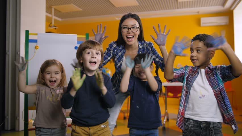 Happy funny multicultural children with smiling teacher showing their hands stained with colorful paint in kindergarten. Portrait of carefree diverse kids with hands in paint posing at art class.   Shutterstock HD Video #1020999349