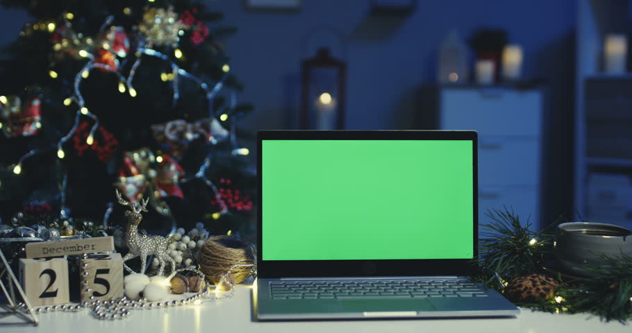 Close up of the laptop computer with a chroma key screen at the magical Christmas tree in the decorated room on Christmas night. Green screen. Alpha channel. Indoors.