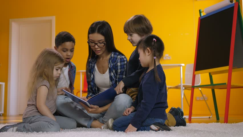 Mixed race teacher in eyeglasses reading book to group of diverse multicultural children in kindergarten while sitting on the floor. Pupils and teacher reading fairy tale together in preschool class.   Shutterstock HD Video #1021045039