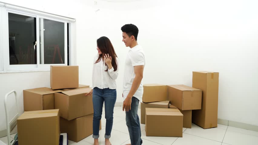 Young man closed woman eyes and showing new house room with pile of cardboard boxes. Shot in 4k resolution #1021048924