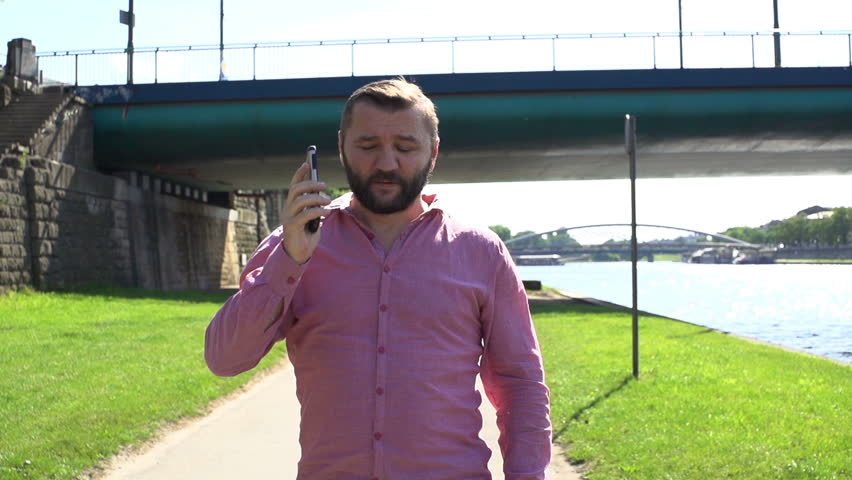 Man with smartphone walking by river in the city, slow motion | Shutterstock HD Video #1021054915